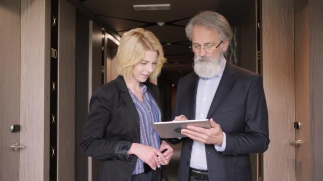 vídeos de stock e filmes b-roll de young businesswoman using digital tablet with male colleague - relação profissional