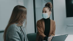young businesswoman using laptop making business plan with colleagues with face masks during COVID-19 pandemic in the office