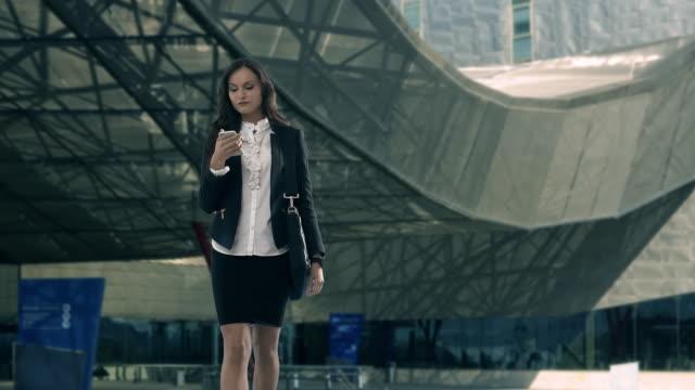 vídeos de stock e filmes b-roll de young businesswoman using smartphone outside office building - saia