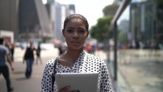 vídeos y material grabado en eventos de stock de joven empresaria usando la tableta en la calle - pardo brasileño