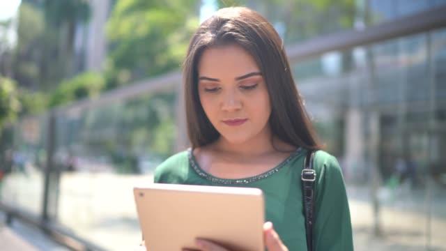 vídeos de stock, filmes e b-roll de mulher de negócios nova que usa a tabuleta na rua - university student