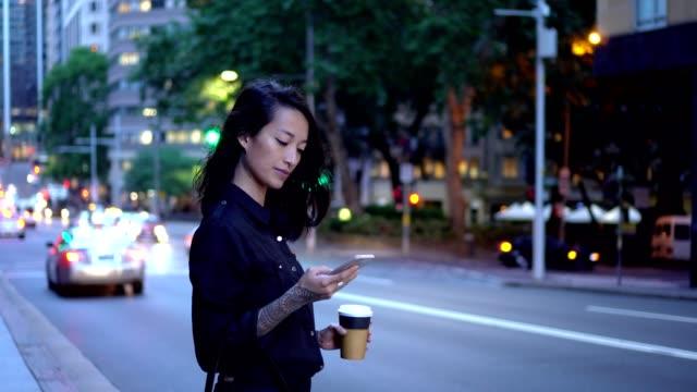 vídeos de stock e filmes b-roll de young businesswoman waiting for taxi in sydney - semáforo de trânsito