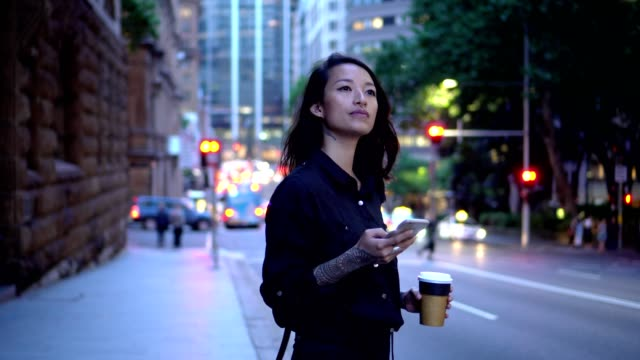 young businesswoman waiting for taxi in sydney - guardare in una direzione video stock e b–roll
