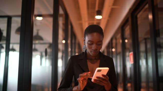 vídeos de stock, filmes e b-roll de jovem empresária andando e digitando no celular no corredor - ir embora