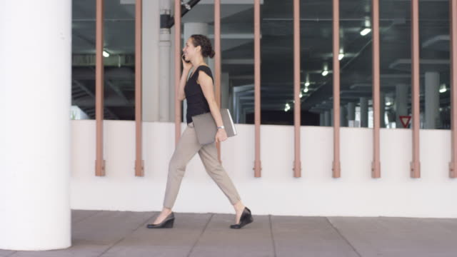 young businesswoman walking walking confidently - multi storey stock videos & royalty-free footage