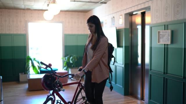 vídeos de stock e filmes b-roll de young businesswoman walking with bicycle at modern office - trabalhadora de colarinho branco