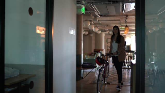 young businesswoman walking with bicycle at modern office - brown hair stock videos & royalty-free footage