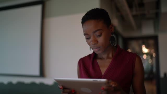 vídeos y material grabado en eventos de stock de joven empresaria caminando con tableta digital en coworking - afro
