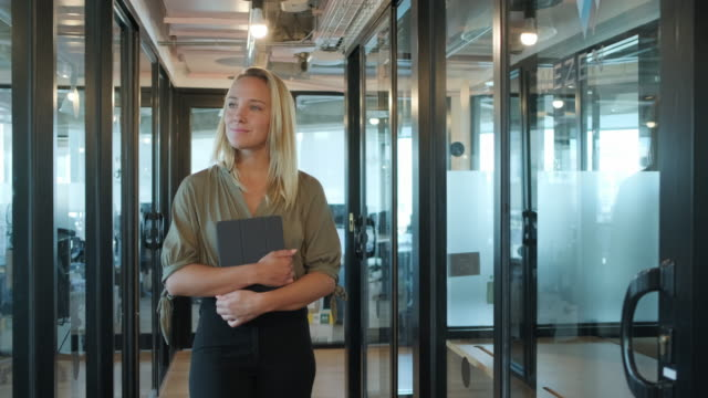 young businesswoman walking with digital tablet in office - stabilized shot stock videos & royalty-free footage