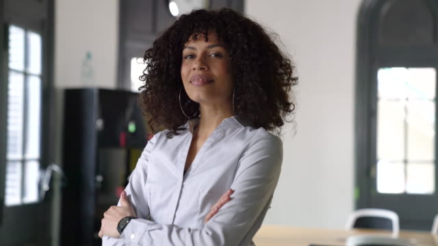 Young businesswoman with arms crossed at office