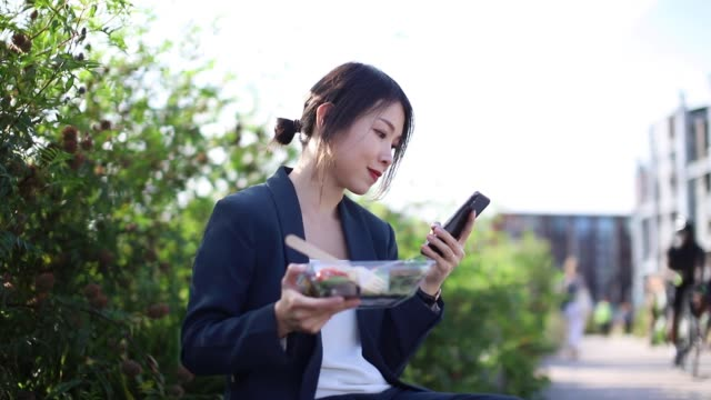 young businesswoman with smart phone, having lunch break at the park - 昼食点の映像素材/bロール