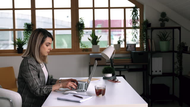 young businesswoman working from her home office setup - hot desking stock videos & royalty-free footage
