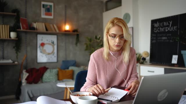 vidéos et rushes de jeune femme d'affaires travaillant de la maison tout en ayant un petit déjeuner et un café - assis