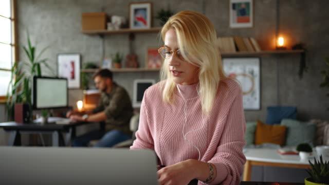 vidéos et rushes de jeune femme d'affaires travaillant de la maison avec son mari travaillant sur un pc dans le backgorund - assis