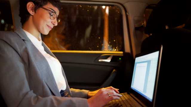 young businesswoman working late at night on her laptop in a car - vehicle seat stock videos & royalty-free footage