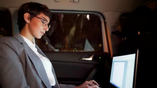 vídeos y material grabado en eventos de stock de joven empresaria trabajando en su portátil en un coche - viaje de negocios