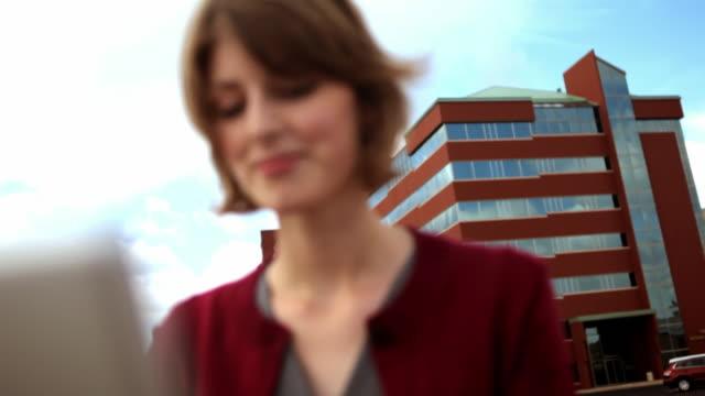 vídeos de stock e filmes b-roll de cu r/f young businesswoman working on laptop outdoors / madison, wisconsin, usa - trabalhadora de colarinho branco