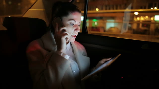 Young businesswoman working on tablet and mobile phone in the car.