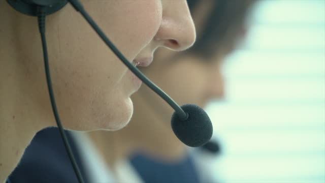 young businesswoman working with a headset and accompanied by her team in call center - telecommunications worker stock videos & royalty-free footage