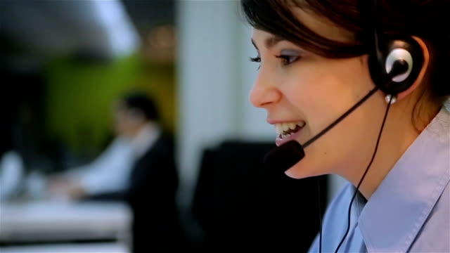 vídeos de stock e filmes b-roll de young businesswoman working with a headset and accompanied by her team in call center. - support