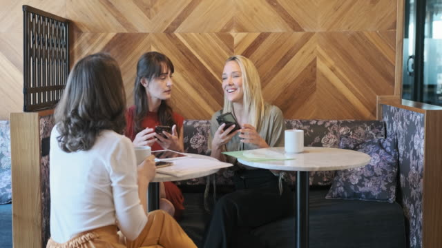 young businesswomen brainstorming in modern office lobby - long hair stock videos & royalty-free footage