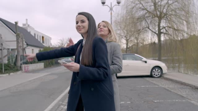 vídeos de stock e filmes b-roll de ms young businesswomen getting into crowdsourced taxi on city street - dividir