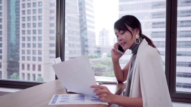 vídeos y material grabado en eventos de stock de mujeres de negocios jóvenes usando el teléfono para comprobar las estadísticas del gráfico del mercado con el equipo - desk