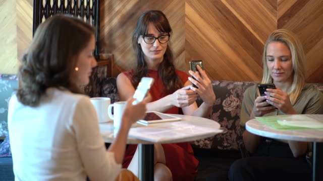 young businesswomen using their smartphones in a coworking space - coffee break stock videos & royalty-free footage