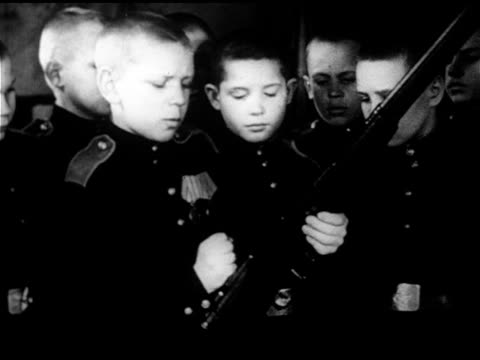 young cadets boy showing others how to pull bolt back on rifle children in uniform marching in snow large group of cadets marching in formation in... - 1953 stock videos and b-roll footage