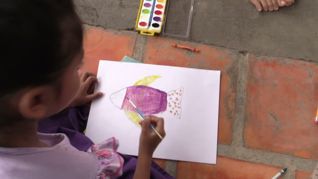 vidéos et rushes de a young cambodian orphan girl paints a fish with watercolor at an orphanage in phnom penh, cambodia - orphelinat