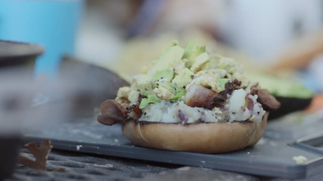 ecu. young camper makes breakfast bagel with avocado and bacon and potato hash. - bacon stock videos & royalty-free footage