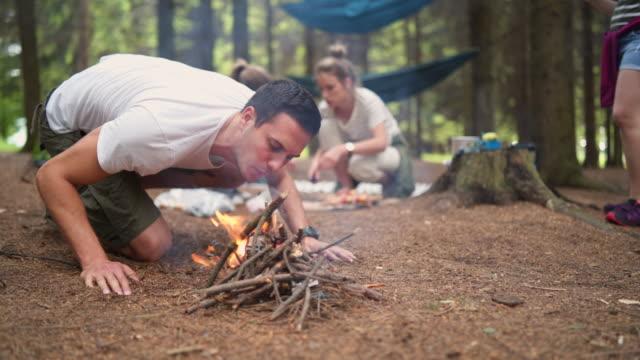 vídeos de stock e filmes b-roll de young camper making campfire - 20 24 anos