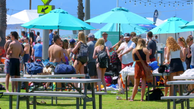 Young campus students enjoy spring break party and relax on Santa Monica Beach in Los Angeles, California