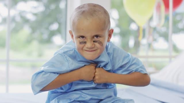 ung cancerpatient visar hans spel ansikte - barndom bildbanksvideor och videomaterial från bakom kulisserna