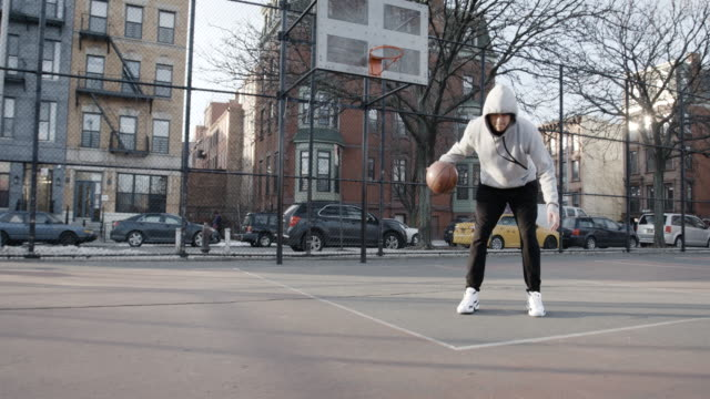 a young candid man practices basketball, alone at a brooklyn court - 4k - sweatshirt stock videos & royalty-free footage