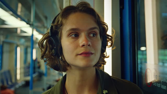 young candid woman listen to music in subway - candid stock videos & royalty-free footage