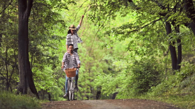 young carefree couple having fun while riding on bicycle through the forest. - young couple stock videos & royalty-free footage