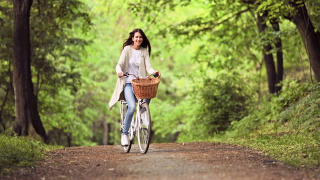 Young carefree woman riding a bicycle through the park.