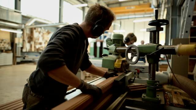 young carpenter at work on a wide belt sander in a carpentry - carpenteria video stock e b–roll