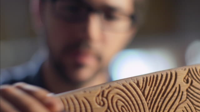 young carpenter brushes curve of wooden skateboard with sandpaper - carpenter stock videos & royalty-free footage