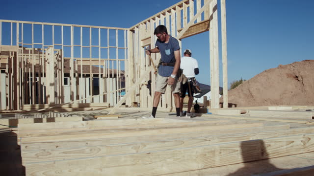 young carpenter construction worker using a pneumatic nail gun to put a wood framed wall together to be raised vertically in a residential home being built on a construction site - work tool stock videos & royalty-free footage