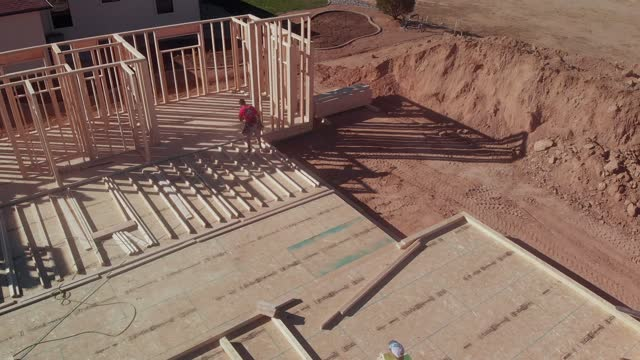 young carpenter construction worker using a pneumatic nail gun to put a wood framed wall together to be raised vertically in a residential home being built on a construction site - incomplete stock videos & royalty-free footage