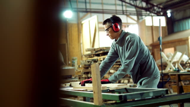 young carpenter sawing timber in workshop - sawdust stock videos and b-roll footage