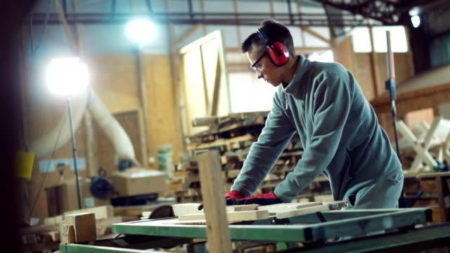 vídeos y material grabado en eventos de stock de joven carpintero sierra la madera en el taller - carpintería