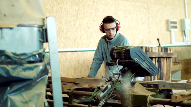 Young carpenter sawing timber in workshop