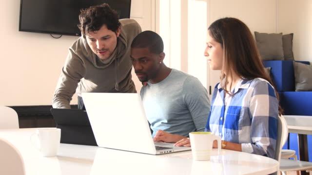 junge casual business-leute in diskussion um laptop und digital-tablette - kleines büro stock-videos und b-roll-filmmaterial