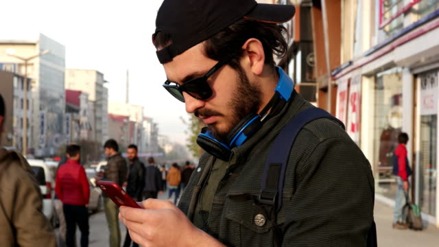 Young casual man using a smart phone in the street