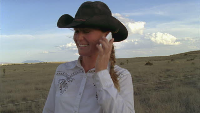 cu young cattle rancher using cell phone, smiling / marfa, texas, usa - nur junge frauen stock-videos und b-roll-filmmaterial