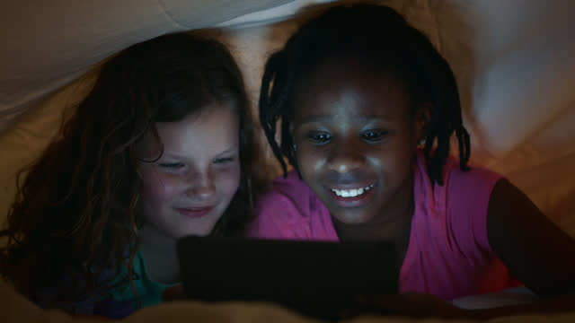 young caucasian and african american friends talk and laugh while watching funny videos on digital tablet under a blanket at sleepover. - slumber party stock videos and b-roll footage