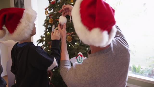 vídeos de stock e filmes b-roll de young caucasian boy helping dad decorate x-mas tree - chapéu do pai natal